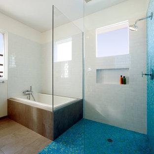 Imagen de cuarto de baño principal, moderno, de tamaño medio, con armarios con paneles lisos, puertas de armario de madera oscura, bañera encastrada, combinación de ducha y bañera, baldosas y/o azulejos azules, baldosas y/o azulejos de vidrio, suelo de baldosas de porcelana, lavabo integrado, encimera de cemento, sanitario de una pieza, paredes blancas, suelo marrón y ducha abierta