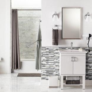 Удачное сочетание для дизайна помещения: главная ванная комната среднего размера в современном стиле с монолитной раковиной, плоскими фасадами, белыми фасадами, столешницей из ламината, ванной в нише, душем над ванной, унитазом-моноблоком, белой плиткой, удлиненной плиткой, белыми стенами и мраморным полом - самое интересное для вас