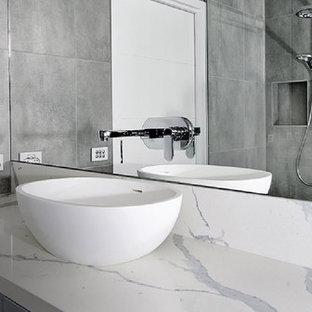 Inspiration för mellanstora moderna vitt badrum, med luckor med infälld panel, grå skåp, grå kakel, bänkskiva i terrazo och ett fristående handfat