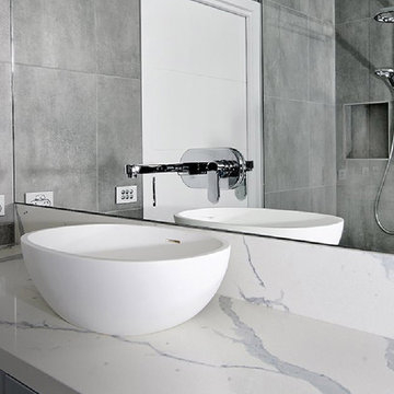 Modern white and grey bathroom with engineered terrazo counter and walls