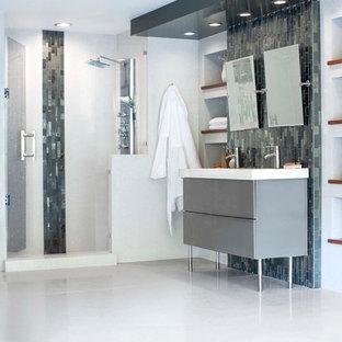 На фото: большие главные ванные комнаты в стиле модернизм с плоскими фасадами, серыми фасадами, душем в нише, серой плиткой, стеклянной плиткой, белыми стенами, столешницей из переработанного стекла и врезной раковиной