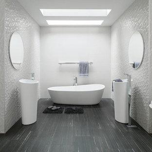 Imagen de cuarto de baño principal, minimalista, grande, con bañera exenta, sanitario de una pieza, baldosas y/o azulejos blancos, baldosas y/o azulejos de porcelana, paredes blancas, suelo laminado, lavabo con pedestal y suelo gris