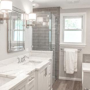 Foto de cuarto de baño con ducha, moderno, de tamaño medio, con armarios con rebordes decorativos, puertas de armario blancas, bañera exenta, paredes grises, suelo de contrachapado, encimera de mármol, suelo gris y encimeras blancas