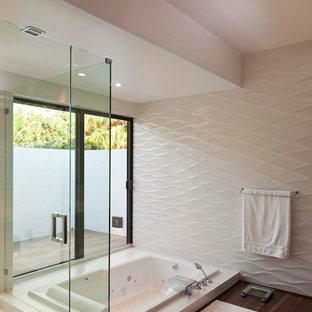 Стильный дизайн: главная ванная комната в стиле модернизм с накладной ванной, угловым душем, белой плиткой, керамической плиткой, белыми стенами, полом из бамбука, коричневым полом и душем с распашными дверями - последний тренд
