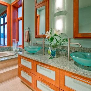 На фото: главная ванная комната в современном стиле с настольной раковиной, стеклянными фасадами, фасадами цвета дерева среднего тона, накладной ванной, зеленой плиткой, столешницей из гранита, зелеными стенами и зеленой столешницей