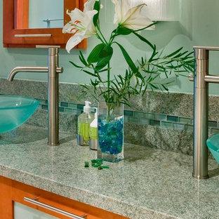 Modelo de cuarto de baño principal, actual, con lavabo sobreencimera, armarios tipo vitrina, puertas de armario de madera oscura, encimera de granito, baldosas y/o azulejos verdes, paredes verdes y suelo de madera en tonos medios