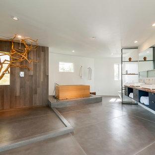 Foto di una grande stanza da bagno padronale minimalista con ante lisce, ante nere, vasca giapponese, doccia aperta, piastrelle grigie, pareti bianche, pavimento in ardesia, lavabo a bacinella e top in legno