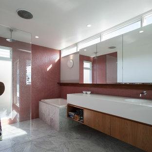 Diseño de cuarto de baño con ducha, contemporáneo, pequeño, con armarios con paneles lisos, puertas de armario marrones, bañera japonesa, ducha abierta, sanitario de pared, baldosas y/o azulejos rojos, baldosas y/o azulejos en mosaico, paredes grises, suelo de mármol, lavabo integrado, encimera de acrílico, suelo gris, ducha abierta y encimeras amarillas