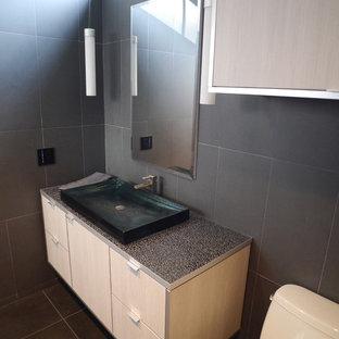 Foto di una sauna moderna di medie dimensioni con lavabo a bacinella, ante lisce, ante in legno chiaro, top in vetro, WC monopezzo, piastrelle in gres porcellanato, pareti grigie e pavimento in gres porcellanato
