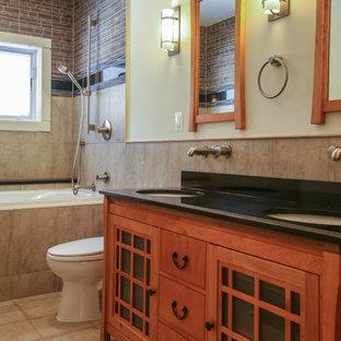 Modelo de cuarto de baño asiático, de tamaño medio, con lavabo bajoencimera, armarios tipo mueble, puertas de armario de madera clara, encimera de granito, bañera encastrada, combinación de ducha y bañera, sanitario de dos piezas, baldosas y/o azulejos marrones, baldosas y/o azulejos de porcelana, paredes blancas y suelo de baldosas de porcelana