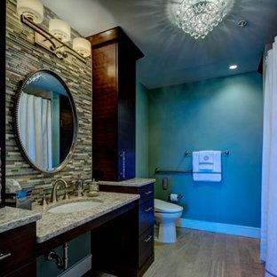 Modelo de cuarto de baño principal, actual, de tamaño medio, con lavabo bajoencimera, armarios con paneles lisos, puertas de armario de madera en tonos medios, encimera de cuarzo compacto, ducha a ras de suelo, sanitario de una pieza, baldosas y/o azulejos multicolor, paredes verdes y suelo de madera clara