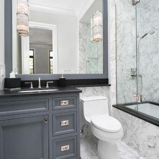 Foto di una piccola stanza da bagno classica con lavabo sottopiano, ante con riquadro incassato, ante grigie, top in granito, vasca sottopiano, WC monopezzo, piastrelle bianche, piastrelle in pietra, pareti grigie e pavimento in marmo