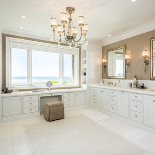 Example of a beach style white tile bathroom design in Orange County with an undermount sink, white cabinets and recessed-panel cabinets