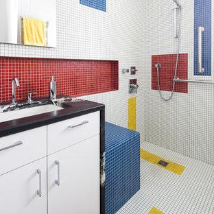 Cette image montre une salle de bain design avec une douche à l'italienne, un lavabo encastré, un placard à porte plane, des portes de placard blanches, un carrelage multicolore, carrelage en mosaïque, un sol en carrelage de terre cuite, un mur multicolore, un plan de toilette en marbre et un banc de douche.