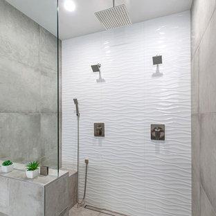 Imagen de cuarto de baño principal, moderno, grande, con armarios con paneles lisos, puertas de armario de madera oscura, bañera exenta, ducha doble, baldosas y/o azulejos grises, baldosas y/o azulejos de travertino, paredes grises, suelo de azulejos de cemento, lavabo sobreencimera, encimera de cuarzo compacto, suelo gris y ducha con puerta con bisagras
