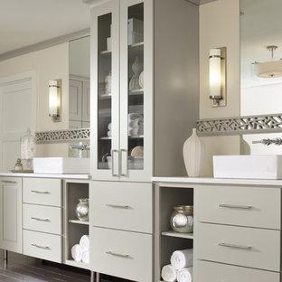 Idée de décoration pour une très grande salle de bain principale design avec un plan vasque, un placard à porte plane, des portes de placard beiges, un plan de toilette en quartz, un mur jaune et un sol en bois foncé.