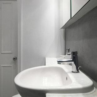 Modelo de cuarto de baño principal, actual, pequeño, con armarios tipo vitrina, puertas de armario blancas, bañera encastrada, combinación de ducha y bañera, sanitario de pared, baldosas y/o azulejos grises, paredes blancas, suelo de cemento, lavabo encastrado, encimera de mármol, suelo gris y ducha con puerta con bisagras
