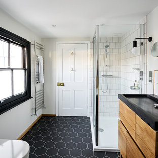 This is an example of a medium sized scandinavian family bathroom in Sussex with flat-panel cabinets, light wood cabinets, a claw-foot bath, a corner shower, a one-piece toilet, white tiles, ceramic tiles, white walls, ceramic flooring, an integrated sink, solid surface worktops, black floors and a hinged door.