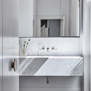 Design ideas for a modern bathroom in Melbourne with white cabinets, white tile, white walls, an undermount sink, a single vanity, a floating vanity, marble, dark hardwood floors, marble benchtops, white benchtops and brown floor.