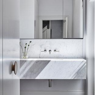 Diseño de cuarto de baño moderno con puertas de armario blancas, baldosas y/o azulejos blancos, paredes blancas, lavabo bajoencimera, baldosas y/o azulejos de mármol, suelo de madera oscura, encimera de mármol, encimeras blancas y suelo marrón