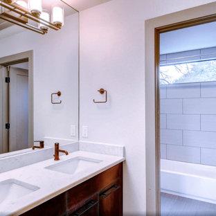 Immagine di una grande stanza da bagno padronale minimal con ante lisce, ante in legno chiaro, vasca ad alcova, vasca/doccia, piastrelle bianche, piastrelle in ceramica, pareti grigie, pavimento in legno massello medio, lavabo integrato e top in quarzite