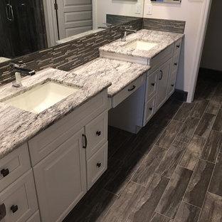 Immagine di una stanza da bagno padronale moderna di medie dimensioni con ante con bugna sagomata, ante bianche, doccia alcova, WC monopezzo, piastrelle grigie, piastrelle in ceramica, pareti bianche, pavimento in compensato, lavabo sottopiano e top in marmo