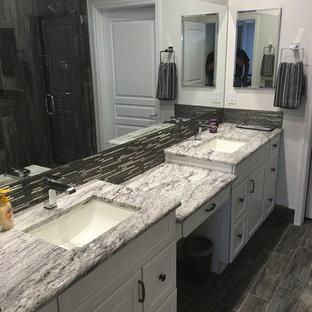 Immagine di una stanza da bagno padronale minimalista di medie dimensioni con ante con bugna sagomata, ante bianche, WC monopezzo, pareti bianche, lavabo sottopiano, top in marmo, doccia alcova, piastrelle grigie, pavimento in compensato e piastrelle in ceramica