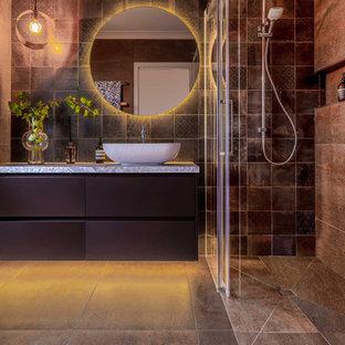 Modern inredning av ett mellanstort flerfärgad flerfärgat en-suite badrum, med släta luckor, bruna skåp, en kantlös dusch, en toalettstol med separat cisternkåpa, brun kakel, porslinskakel, bruna väggar, klinkergolv i porslin, ett fristående handfat, bänkskiva i kvarts, brunt golv och dusch med skjutdörr