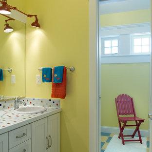 Immagine di una stanza da bagno per bambini costiera con lavabo da incasso, ante con riquadro incassato, ante bianche, top piastrellato, vasca/doccia, piastrelle multicolore, piastrelle in ceramica, pareti gialle e top multicolore