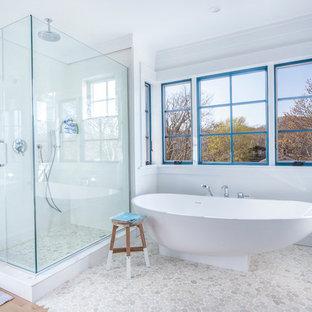 Bild på ett maritimt en-suite badrum, med ett fristående badkar, en hörndusch, kakel i småsten, vita väggar, öppna hyllor, skåp i mellenmörkt trä, grå kakel, vit kakel, mellanmörkt trägolv, ett undermonterad handfat, bänkskiva i kvarts och dusch med gångjärnsdörr