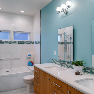 Bathroom - mid-sized contemporary kids' white tile and porcelain tile porcelain tile and double-sink bathroom idea in San Francisco with flat-panel cabinets, light wood cabinets, a one-piece toilet, blue walls, an undermount sink, quartz countertops, a hinged shower door, white countertops, a niche and a floating vanity