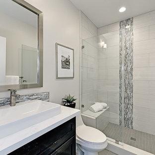 Imagen de cuarto de baño con ducha, tradicional renovado, con puertas de armario negras, ducha empotrada, paredes grises, lavabo sobreencimera, armarios con paneles empotrados, sanitario de una pieza, encimera de mármol, baldosas y/o azulejos blancos, ducha abierta y encimeras blancas