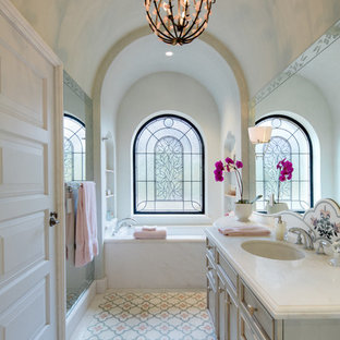 Mediterranean bathroom in San Francisco with grey cabinets, a submerged bath, an alcove shower, beige tiles, pink tiles, multi-coloured floors and a hinged door.