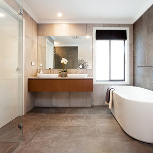 This is an example of a contemporary master bathroom in Sydney with flat-panel cabinets, medium wood cabinets, a freestanding tub, gray tile, grey walls, a vessel sink and grey floor.