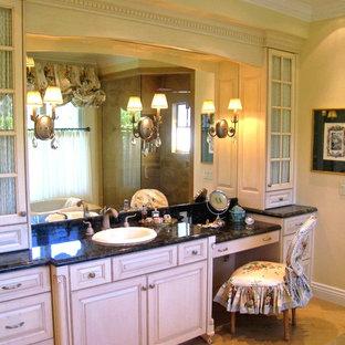 Foto di una grande stanza da bagno padronale shabby-chic style con ante con bugna sagomata, ante beige, vasca freestanding, doccia ad angolo, piastrelle nere, lastra di pietra, pareti gialle, pavimento in gres porcellanato, lavabo da incasso, top in granito e pavimento beige