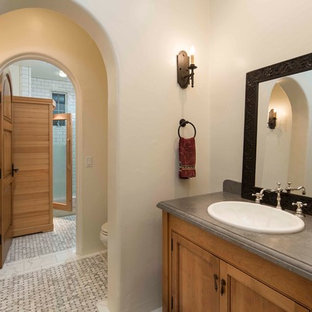 Inspiration for a large mediterranean ensuite bathroom in Santa Barbara with recessed-panel cabinets, medium wood cabinets, a walk-in shower, a two-piece toilet, metro tiles, white walls, mosaic tile flooring and a built-in sink.