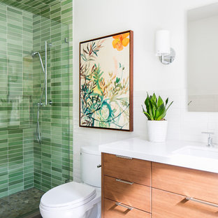 Exempel på ett 50 tals vit vitt badrum med dusch, med skåp i mellenmörkt trä, en dusch i en alkov, grön kakel, vita väggar, bänkskiva i kvarts, dusch med gångjärnsdörr, släta luckor, klinkergolv i småsten, ett undermonterad handfat och grått golv