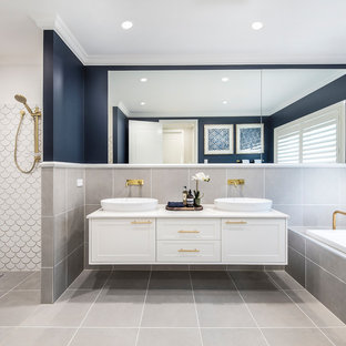 This is an example of a beach style master bathroom in Brisbane with shaker cabinets, white cabinets, a drop-in tub, gray tile, blue walls, a vessel sink, grey floor and white benchtops.