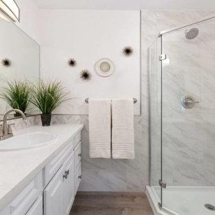 他の地域の中くらいのコンテンポラリースタイルのおしゃれなバスルーム (浴槽なし) (レイズドパネル扉のキャビネット、白いキャビネット、コーナー設置型シャワー、一体型トイレ、マルチカラーのタイル、磁器タイル、ピンクの壁、ラミネートの床、オーバーカウンターシンク、珪岩の洗面台、茶色い床、開き戸のシャワー、白い洗面カウンター、洗面台1つ、独立型洗面台) の写真