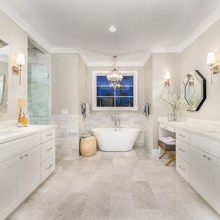 Idéer för ett stort klassiskt en-suite badrum, med luckor med infälld panel, vita skåp, ett fristående badkar, en dusch i en alkov, stenkakel, beige väggar, ett undermonterad handfat och dusch med gångjärnsdörr
