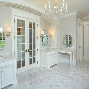 Klassisk inredning av ett stort en-suite badrum, med ett undermonterad handfat, luckor med upphöjd panel, vita skåp, vit kakel, beige väggar och marmorgolv