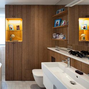 Idée de décoration pour une salle de bain design avec un placard à porte plane, des portes de placard blanches, un plan vasque et un sol gris.