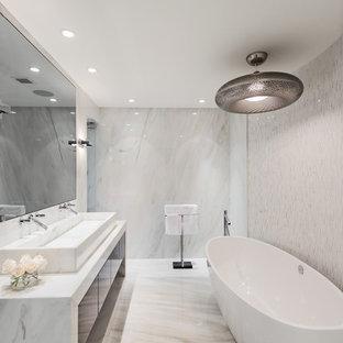 Idee per una stanza da bagno design con lavabo rettangolare, ante lisce, ante marroni, top in marmo, vasca freestanding, WC monopezzo, piastrelle bianche e piastrelle di marmo