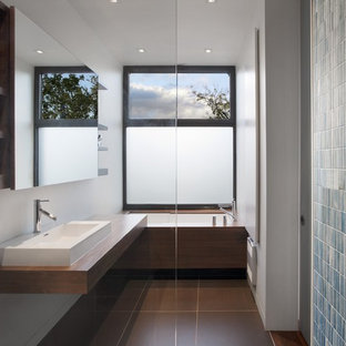 Photo of a modern bathroom in Montreal with a vessel sink, wooden worktops, an alcove bath, blue tiles and open cabinets.