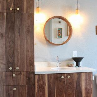 Modelo de cuarto de baño retro, de tamaño medio, con armarios con paneles lisos, puertas de armario de madera oscura, bañera empotrada, combinación de ducha y bañera, sanitario de dos piezas, baldosas y/o azulejos grises, baldosas y/o azulejos de porcelana, paredes azules, suelo de cemento, lavabo bajoencimera, encimera de cuarzo compacto, suelo naranja, ducha con cortina y encimeras blancas