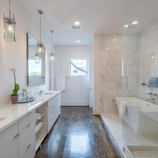 Inredning av ett klassiskt stort vit vitt en-suite badrum, med vita skåp, ett fristående badkar, en öppen dusch, vit kakel, vita väggar, ett undermonterad handfat, bänkskiva i kvarts, mörkt trägolv, med dusch som är öppen, möbel-liknande, en toalettstol med separat cisternkåpa, marmorkakel och brunt golv