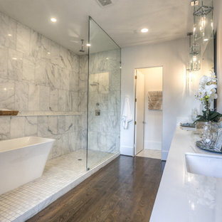 Inspiration for a large transitional master bathroom in Houston with an undermount sink, a freestanding tub, an open shower, dark hardwood floors, an open shower, furniture-like cabinets, a two-piece toilet, white tile, marble, white walls, engineered quartz benchtops, brown floor and white benchtops.