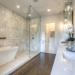 Großes Klassisches Badezimmer En Suite mit Unterbauwaschbecken, freistehender Badewanne, offener Dusche, dunklem Holzboden, offener Dusche, verzierten Schränken, Wandtoilette mit Spülkasten, weißen Fliesen, Marmorfliesen, weißer Wandfarbe, Quarzwerkstein-Waschtisch, braunem Boden und weißer Waschtischplatte in Houston