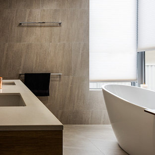 Inspiration for a contemporary 3/4 bathroom in Sunshine Coast with medium wood cabinets, a freestanding tub, gray tile, grey walls, an undermount sink, grey floor, grey benchtops, stone tile and a double shower.