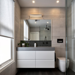 Photo of a mid-sized contemporary 3/4 bathroom in Melbourne with white cabinets, a wall-mount toilet, gray tile, porcelain tile, an integrated sink, black floor, grey benchtops, a single vanity and a floating vanity.
